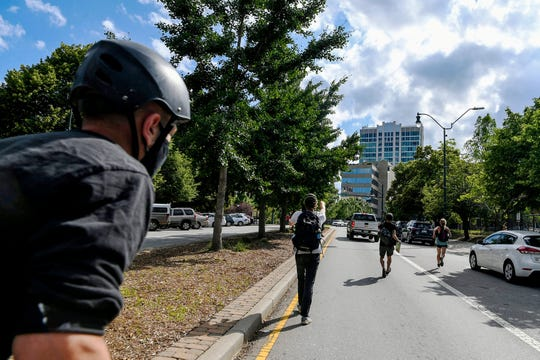 People chase after a pickup truck after the driver pushed through protesters June 9, 2020 in downtown Asheville.