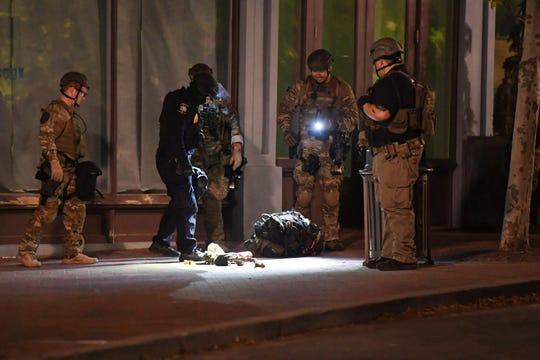 Law enforcement look at the belongings of a man arrested while walking through Pack Square after curfew June 2, 2020.