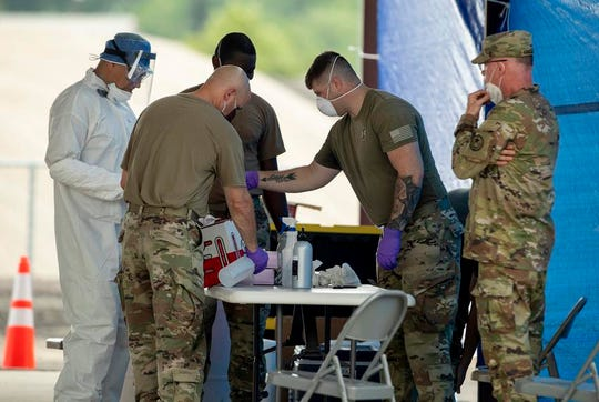 Soldiers with the Texas National Guard work at a drive-thru coronavirus testing center in Smithville.