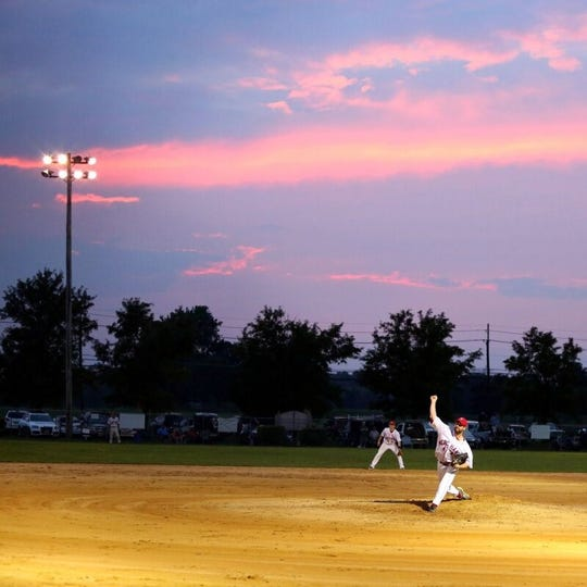 The sun sets over the field as Vincentown's Zeke Boren pitches during the 2013 Rancocas Valley Baseball League championship series.