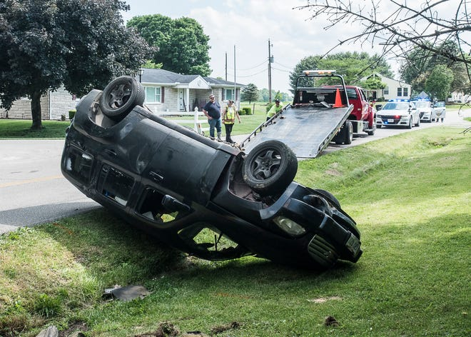 A tow truck driver flips a car upright after it flipped over on Charleston Pike Wednesday afternoon on June 10, 2020.