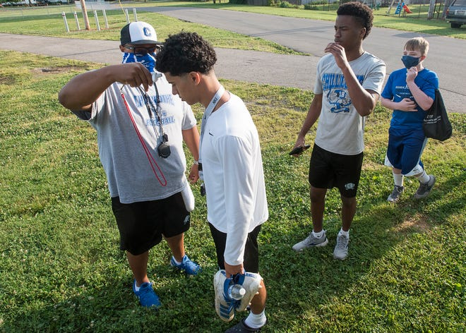 Head Chillicothe football coach Douglas Pryor takes the temperatures of his athletes before they start practice on June 9, 2020. The athletes started their second day of skills practice.