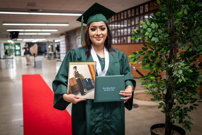 Shelby Mireno holds a photograph of her brother, North High class of 2020 graduate Henry Minero, after collecting his diploma Sunday at the school's graduation ceremony. Henry, who is currently in U.S. Marine Corps boot camp, was unable to attend the ceremony. Henry filled in for his sister during her graduation ceremony in 2018 when she was undergoing chemotherapy treatment for leukemia.