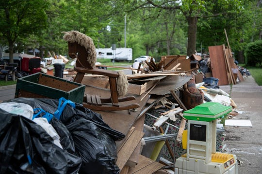 Flood damaged drywall, flooring and people's belongings are being put outside of home for pickup on Perrine Road on the northwest side of Midland, Thursday, May 28, 2020.