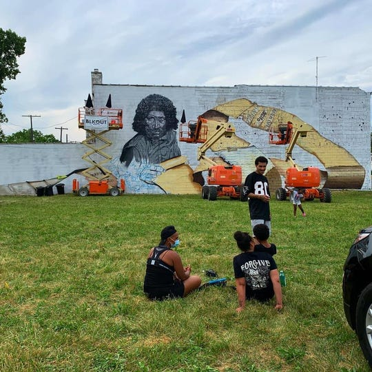 People watch as a new Malice Green mural takes shape in Detroit. Artist Sydney James plans to have it done by Juneteenth, or June 19, the holiday marking the end of slavery in the United States.