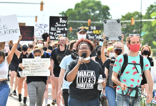 Organizer Nakia Wallace leads chants while protesters march against police brutality in Detroit on June 10, 2020. This is the 13th day of protesting in Detroit.