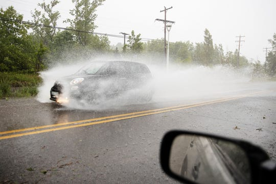 A car drives through water over Ottawa Beach Road in Holland on Wednesday, June 10, 2020. A severe storm blew through the area downing trees and power lines.