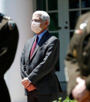 Dr. Anthony Fauci, director of the National Institute of Allergy and Infectious Diseases, listens as President Donald Trump speaks about the coronavirus in the Rose Garden of the White House in this May 15, 2020, file photo.