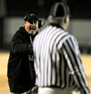 Henderson County coach Clay Clevenger talks to the referee on the sidelines during the 2010 6-A regional championship game at Male.