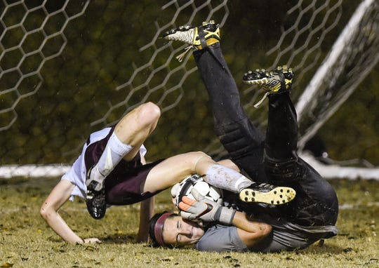 Murray goalkeeper Meredith Purdom makes the save as Henderson County's Darby O'Nan tumbles over her during the 2015 first round state tournament game in Henderson.
