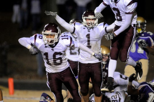 Henderson County's Jamal Hill, Mitchell Gabe and Victor Cosby, from left, celebrate a goal-line stand in the 2010 6-A regional championship game at Male.