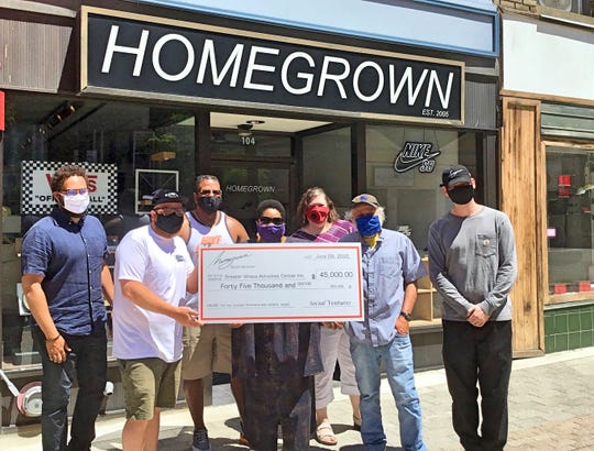 """Homegrown Skateshop owner Andrew Douglas, far right, and Jeff Furman, former Ben & Jerry's Board of Directors chairman, left of Andrew, presented a $45,000 check to The Greater Ithaca Activities Center during a ceremony held Tuesday in front of the shop.  Homegrown raised the funds by hosting a raffle to win a pair of Ben & Jerry's X Nike SB Dunk Low """"Chunky Dunky"""" sneakers."""