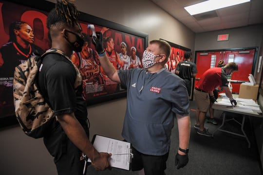 B.J. Duplantis, an associate director of sports medicine at UL, conducts a temperature check on a Ragin' Cajuns football player before voluntary workouts opened last week.