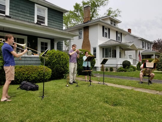 A brass quartet, led by husband and wife Jesse and Julie Heetland, center, with Ben Factor on trombone, far left, and Tom Theller, far right, on tuba, performs on a Sunday afternoon in May. The group has been playing nearly every weekend since Easter outside the Heetland's home in Lancaster during the ongoing coronavirus pandemic.