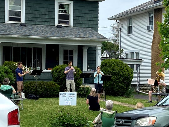 Local residents gather to listen to a brass quartet, led by husband and wife Jesse and Julie Heetland, center, with Ben Factor on trombone, far left, and Tom Theller, far right, on tuba, perform on a Sunday afternoon in May. The group has been playing nearly every weekend since Easter outside the Heetland's home in Lancaster during the ongoing coronavirus pandemic.