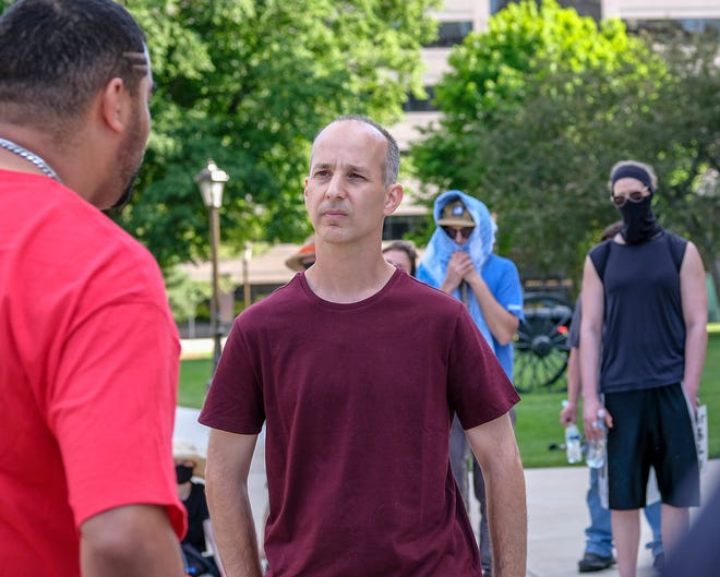 Lansing Mayor Andy Schor listens to protest organizer Paul Birdsong on the grounds of the State Capitol Sunday, June 7, 2020.