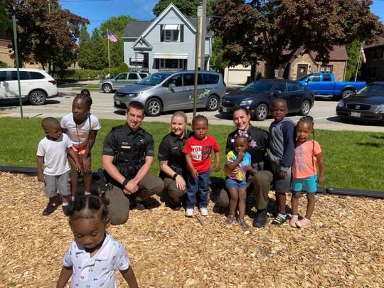Local law enforcement officers pose with a group of children during the community barbecue in Washington Park on June 6.