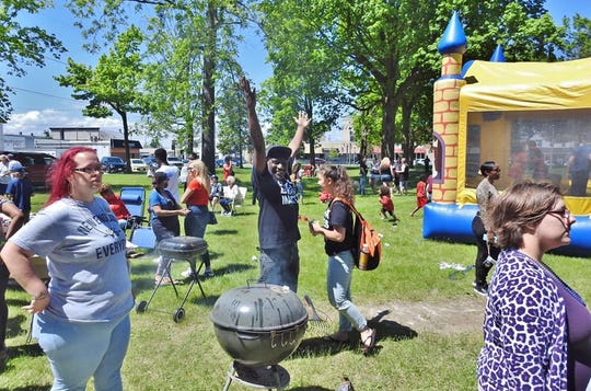 One man poses for the camera as others mill around Washington Park during the community barbecue June 6.