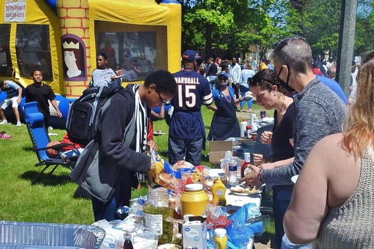 People get food at the community barbecue in Washington Park on June 6.