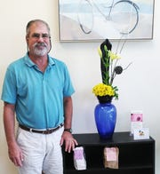 Bruce Neustadt, owner of Cache Cleaners, with Connie Lowery's striking design for National Garden Week.