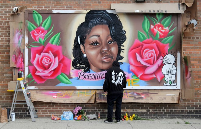 Artist Chris Burke works on a mural of Breonna Taylor on East Locust and North Holton streets in Milwaukee.