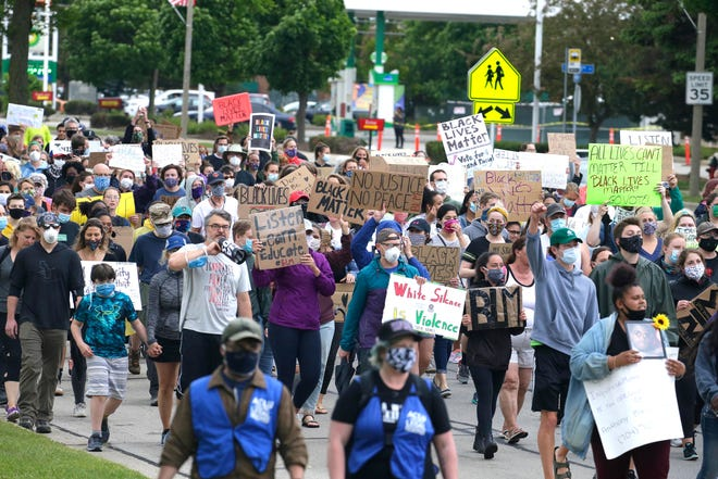 Protesters march from North 124th Street and West North Avenue to the Wauwatosa Police Department to draw attention to racial injustice and police brutality.