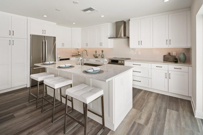 The kitchen of the revamped villa has quartz countertops with plenty of work space and Euro-style white cabinetry.