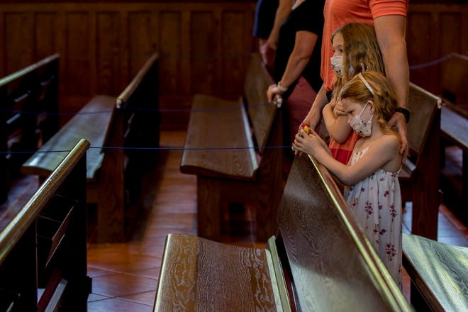 Dr. Tim Miller stands with his arms around his daughters, Avery and Sydney during mass at St. Edwards in Granville. The Church started holding mass again but with some differences. Many of the pews are roped off to help keep to social distancing guidelines. All parishioners must wear face coverings and wash their hands as they enter the church and there is no hand shaking.