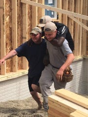 Marine Corporal Melroy Cort, who lost both legs while serving in Iraq, is carried by volunteers from A Soldier's Journey Home, up into the smart home being built for him and his family near Etna in western Licking County. Cort wanted to at least get into the house and nail down some boards.