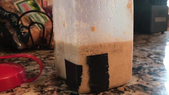 Tape marks show how much the sourdough starter has risen.