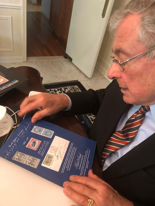 "Ronald Bassey looks at the auction catalog that holds an image of the famous ""inverted Jenny"" postage stamp he has secretly owned and kept in a bank vault for more than 40 years and which is expected to sell July 1, 2020 for at least $200,000."