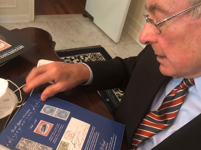 """Ronald Bassey looks at the auction catalog that holds an image of the famous """"inverted Jenny"""" postage stamp he has secretly owned and kept in a bank vault for more than 40 years and which is expected to sell July 1, 2020 for at least $200,000."""