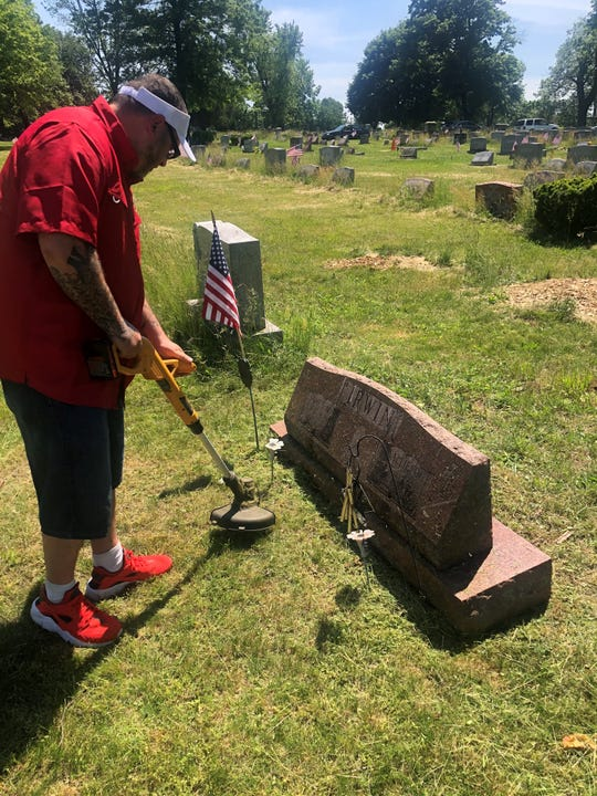 Jim Irwin of Lebanon uses his weed whacker on the grass around the grave of his grandfather, a World War II veteran.