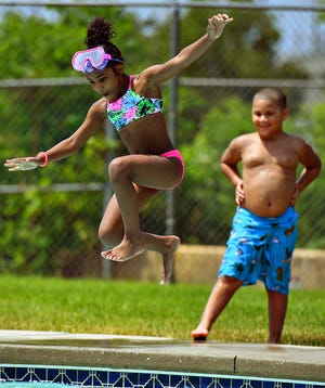 Azure Boxley, 7, right, looks on as Quea Hart, 8, both of York City, jumps into the pool at Graham Aquatic Center-YMCA in York City, Wednesday, June 10, 2020. Dawn J. Sagert photo