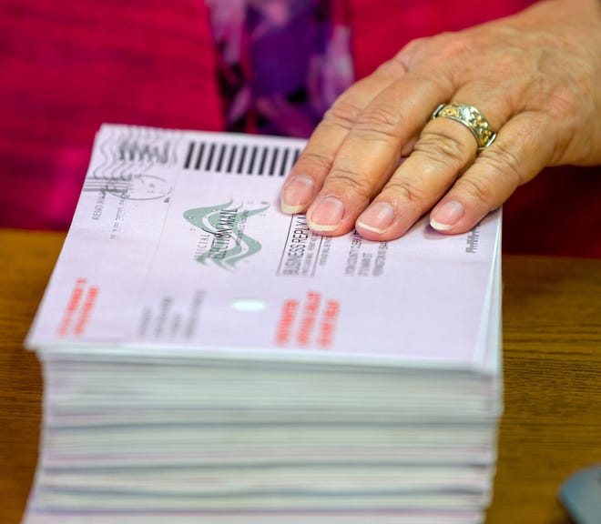 Stacks of ballot envelopes are separated for scanning.
