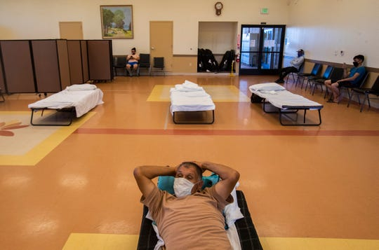 A farmer gets ready to rest for the night at the Galilee Center, a migrant shelter that houses migrant workers who travel into the Coachella Valley from other parts of the state and from Mexicali, Mexico. The shelter has set up beds with 6 feet of distance between as a precaution against COVID-19.