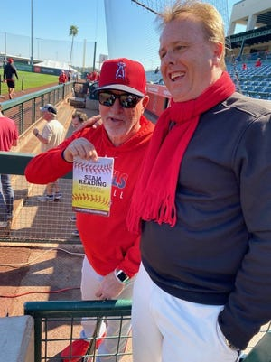 Dennis Tiefenthaler, right, with Angels manager Joe Maddon and a copy of his book 'Seam Reading'.
