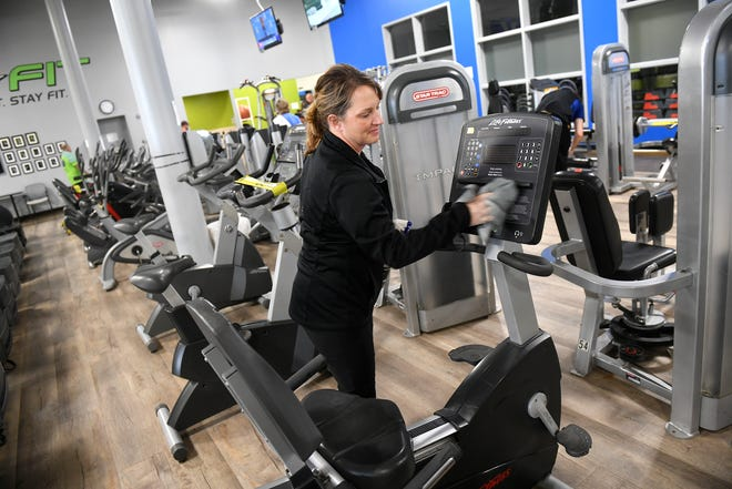 Lori Fuchs cleans equipment at STa-FIT Wednesday, June 10, 2020, in Sartell.