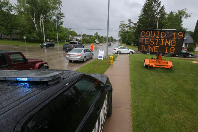 Cars line up for a drive-thru COVID-19 test site on Wednesday, June 10, 2020, along County Highway HH in Stevens Point, Wis. The drive-thru test site was set up in response to an outbreak connected to a local graduation party.