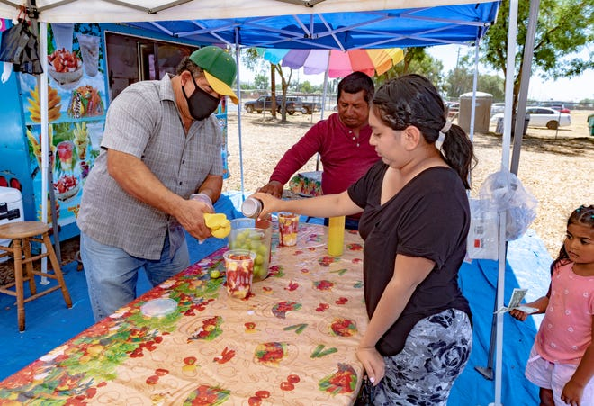 Jose Gonzalez, left, prepares fruit cocktails for customers at La Tropical on Wednesday, June 10, 2020 at the Tulare County Fairgrounds Swap Meet. It will be open each Wednesday at 10 a.m. after being closed for COVID-19 concerns.
