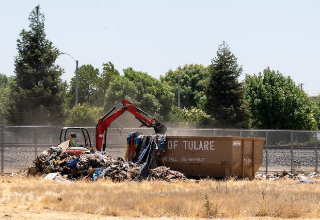 Heavy equipment transfers a debris pile to a dumpster along the railroad tracks between Cross and Pleasant streets Wednesday, June 10, 2020. The area is often inhabited by homeless.