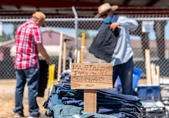 A man shops pants as vendors reunite with shoppers Wednesday, June 10, 2020 at the Tulare County Fairgrounds Swap Meet. It will be open each Wednesday at 10 a.m. after being closed for COVID-19 concerns.