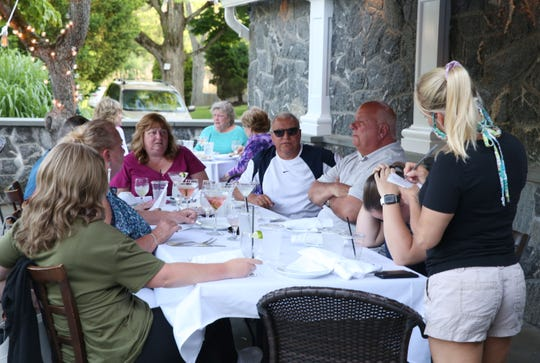 A waitress takes orders as people enjoy outdoor dining at Traditions 118 Restaurant on Tomahawk Street in Somers June 9, 2020. Tuesday was the first day restaurants could open up with outside dinning.