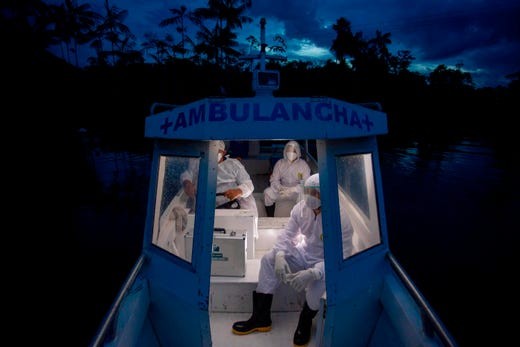Health workers from the city of Melgaco ride a boat ambulance on their way back after visiting eight families that live without electricity in a small riverside community at the Quara river, amid concern over the spread of the COVID-19 coronavirus, in the southwest of Marajo Island, Brazil, on June 9, 2020.