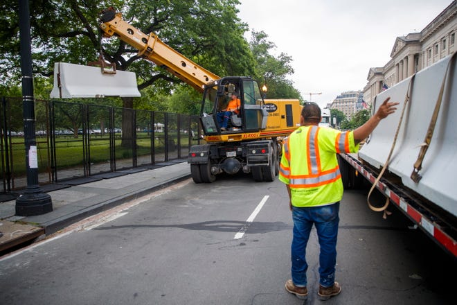 A crane lifts concrete barriers onto a flatbed truck in the first step to removing the temporary fencing around the White House grounds and Lafayette Park in Washington, DC, June 10, 2020. Work crews have started to remove the fencing that was erected around the White House grounds and Lafayette Square during the protests over the death of George Floyd in police custody.