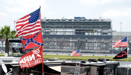 Confederate and American flags fly on top of a motor home at Daytona International Speedway in 2015.