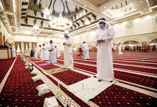 Muslim worshippers, distanced safely from each other and clad in face masks due to the COVID-19 coronavirus pandemic, perform the noon prayers at a mosque in Kuwait City on June 10, 2020 for the first time since a lockdown was instated three months ago.
