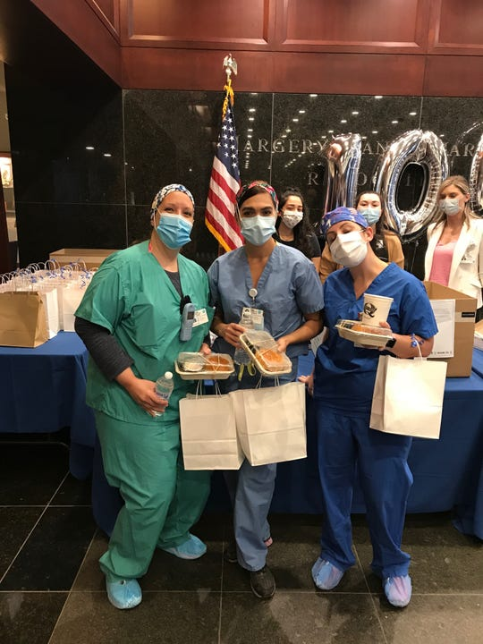 Health care workers at Hackensack University Medical Center enjoy a meal from Mighty Quinn's Barbeque.