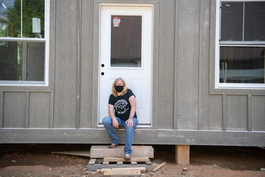 """Amy Cantrell, co-director of BeLoved Asheville poses outside of the model home of the future BeLoved Asheville Village in East Asheville on June 11, 2020. The site is planned to include 12 micro-homes of about 440-square feet. Cantrell describes the homes as """"deeply affordable housing"""" designed with equity building in their rental plans."""