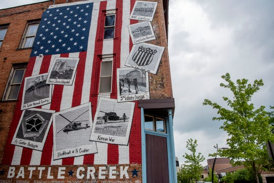 """Storm clouds roll over a mural titled """"Salute to the Military History of Battle Creek"""" on Wednesday, June 10, 2020 in Battle Creek, Mich. Fort Custer is named after General Armstrong Custer, who led the Michigan Calvary Brigade in the civil war, and murdered Native Americans in the American Indian Wars."""